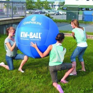 ballon de kin ball bleu géant et personnes jouent dans l'herbe