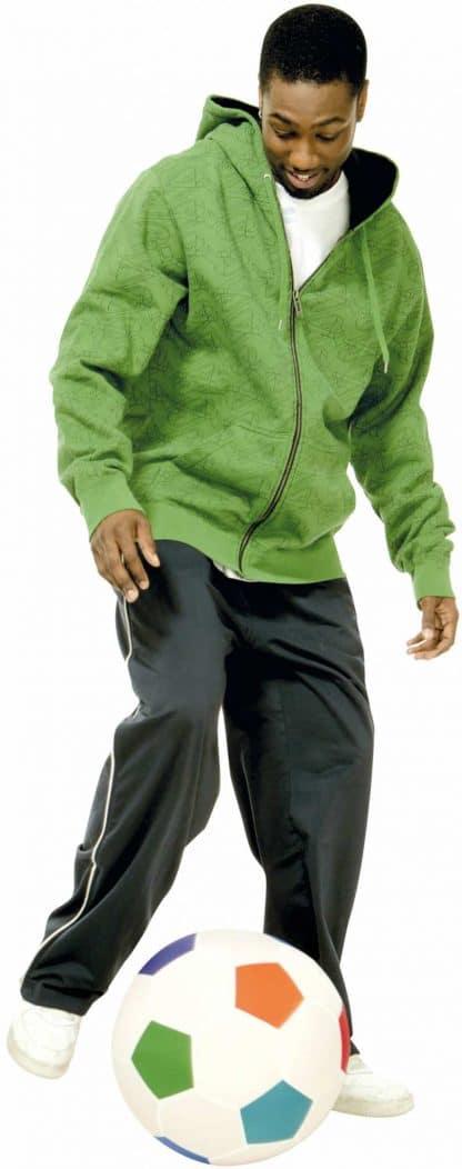 adolescent veste verte joue avec ballon de foot par terre