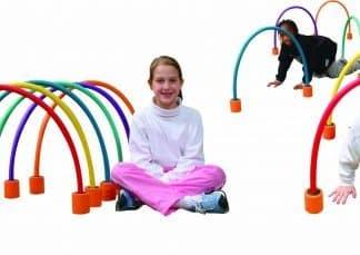 Enfants rampe et jambes croisés dans parcours arceaux en mousse demi-cercles